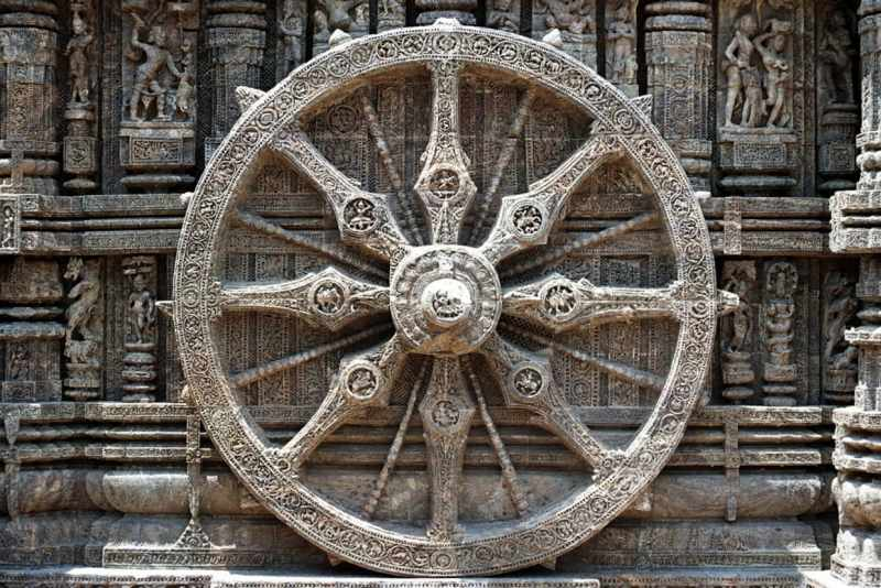 Pushing a large ancient stone wheel.